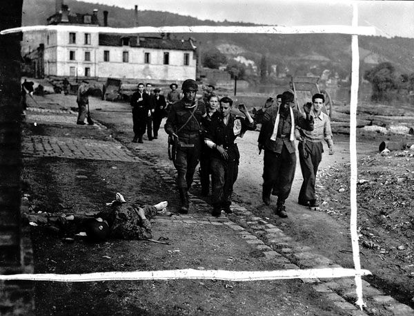 German prisoners passing a dead Waffen SS soldier, Elbeuf, France, 27 August 1944.