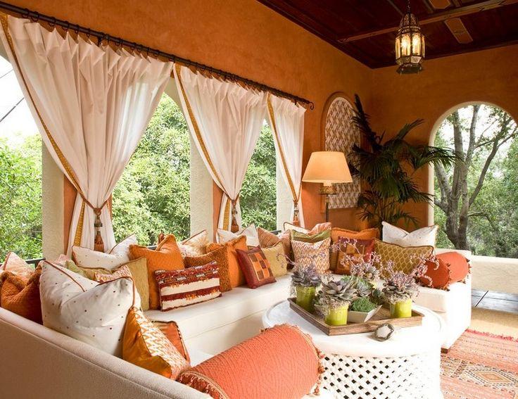 rideau véranda blanc aux accents dorés, canapé en U, peinture ocre et coussins assortis