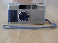Released in 1990, The Contax T2 was the second of the Contax T series of high-end compact film cameras targeted at the professional and luxury consumer markets. The Contax T2 was offered in in champagne silver, black and gold plated finishes. The Contax T2 was renowned for its Carl Zeiss T* multi-coated Sonnar 2.8/38 lens comprising 5 elements in 4 groups and user friendly controls. While it offered full automation, including Autofocus and Program AE, the Contax T2 was one of the most...