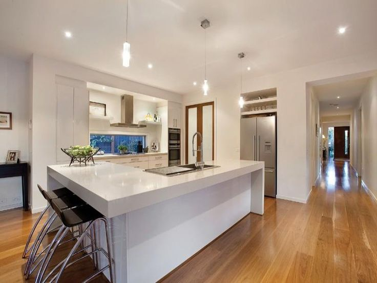 White kitchen, glass splashback. Doors to pantry. Wooden floors. Want this kitchen.