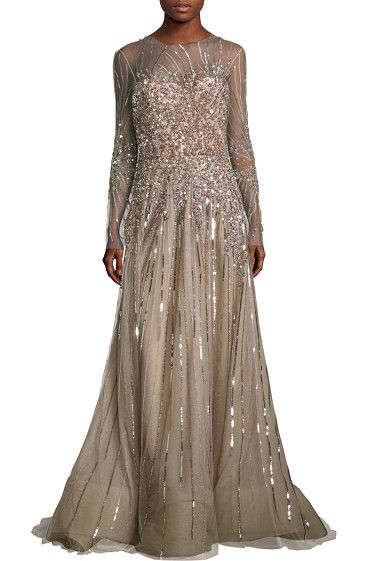 "Embellished tulle gown by Reem Acra. Radiant tulle gown with shimmering sequin accents. Roundneck. Long sleeves. Concealed back zip closure. About 65"" fro..."
