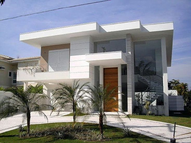 Casa com dois pavimentos, beiral branco, grandes aberturas em vidro e porta em madeira, jardim frontal com coqueiros/ palmeiras.