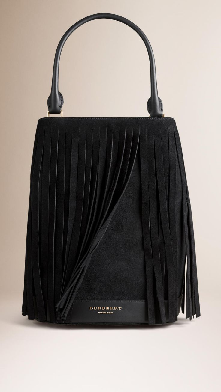 The Bucket Bag in suede with overlaid fringing and detachable leather wristlet. A runway icon designed in London and crafted in Italy. Hand-finished details capture the collection's bohemian attitude.