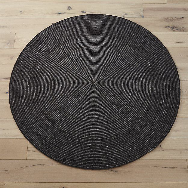 Shop circle rug 6'.   Graphic circle rounds out the room.  Tinted carbon grey, strips of 100% cotton are handwoven into braids, spiraling from the center with white zigzag stitching.
