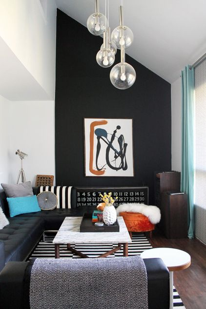 """Jet black in Montreal. The accent wall in Sarah Brown and Chad Zentner's large, open-concept living room was originally covered in faux-wood wallpaper and two layers of faux-brick wallpaper. """"Removing the layers of wallpaper from the very high feature wall in the living room was challenging and something I hope to never have to repeat,"""" says Brown. But the result, this wall with a dramatic jet-black hue, was certainly worth it."""