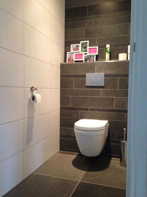 Zwarte vierkante vloertegels. Witte muur. Zwarte wandje, grote rechthoekige en kleine langwerpige tegels.
