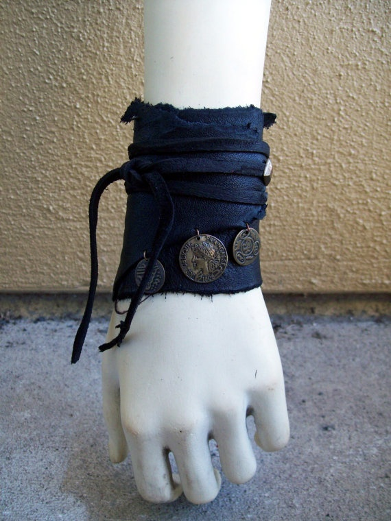 Raven Coin Cuff by ArchaicLeatherworks, $12.00 -- Made from recycled scraps of black cowhide, hand cut lace, dark brass hardware, and coins from a thrift store bracelet this simple wrap cuff is adjustable to any size.