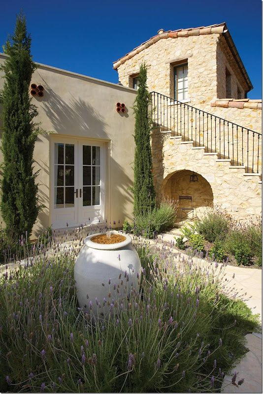 Mediterranean style garden to compliment the home.  white urn water feature with blooming lavender around it.  If only lavender would grow here in FL.. I'd use it in every design!