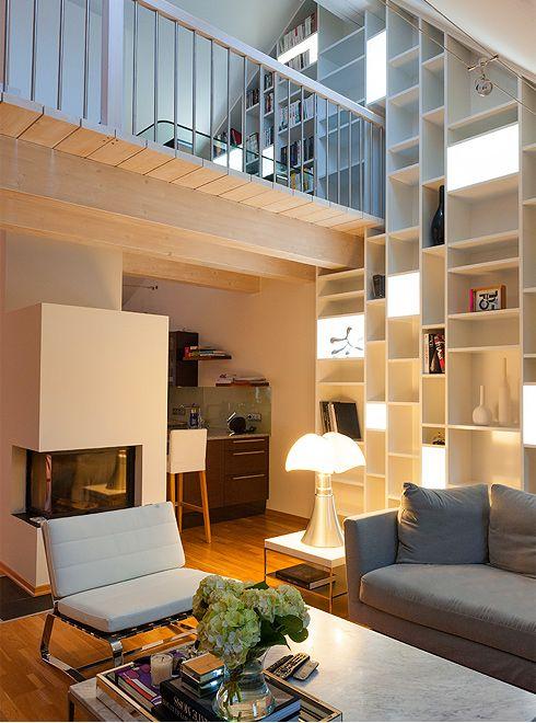 Uitwerking van een boekenkast op maat met loopbrug : Marie en Karel wonen in een mooi appartement, verscholen onder de daken van de stad Mechelen. De ruimte is verdeeld over 2 niveaus, rond een loopbrug op mezzanineniveau, waardoor de verschillende delen van de ruimte bijzonder open en licht zijn. Hun wens? Een grote boekenkast die uitkijkt op de zitkamer en ook geïntegreerd is in de loopbrug.