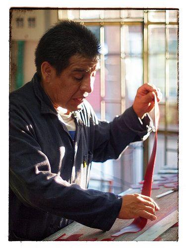 Germán, en la fábrica, cortando cuero.