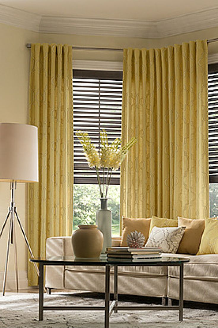 """Finish off your living room with window coverings that provide just the right amount of texture and color balance. The 2"""" wood blinds are from Graber's Letta Collection (in Harbor Grey #1761). The blinds feature cord lift, cord tilt and a 3"""" classic valance. Also shown are Graber's soft drapes in Isabelle (#3760) with back tabs."""