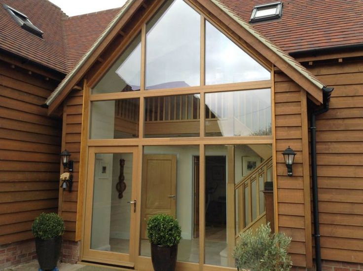 Gable End Featuring Fixed Glass Windows And Entrance Door