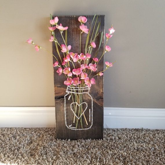 Mason Jar String art with Artificial Flowers  Wood is stained & slightly distressed along edges Approx 18x7x1 Mason Jar is strung in white string with silver nails. Hang this in your home for some Farmhouse chic charm :) Perfect to liven up your house for spring