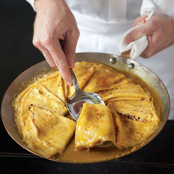 Crêpes are folded and set afloat in a sweet orange-butter sauce and then set aflame in this classic French dessert.