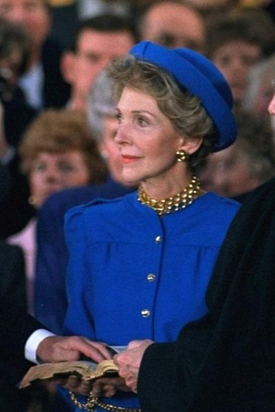 First Lady Nancy Reagan looks on as President Ronald Reagan is sworn in ...