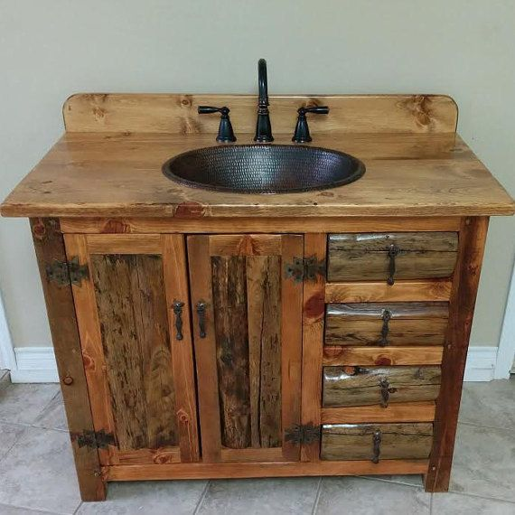 this rustic bathroom vanity features a hammered copper sink and a bronze faucet and a stack