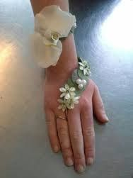 A clever and unusual corsage idea, and very feminine. Pearls or jewels could be worked onto ribbon leading to finger.