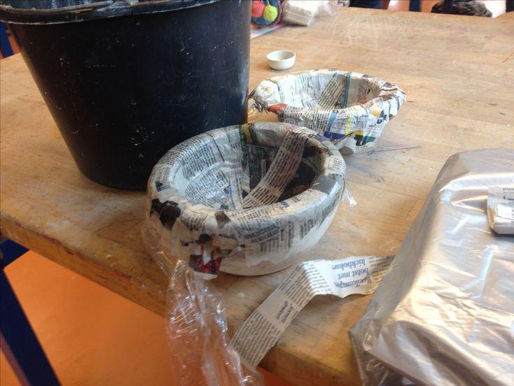 Hier de ene kant van de gemaakte wereldbol nog in de mal de andere kant is al klaar met de papier maché.