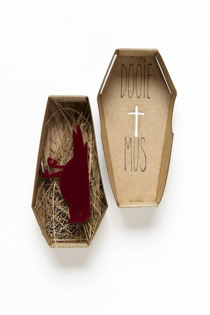 The necklace of the Dooie Mus (dead sparrow) comes in this awesome cardboard packaging. Yes, it is a coffin. Black comedy at it's finest.