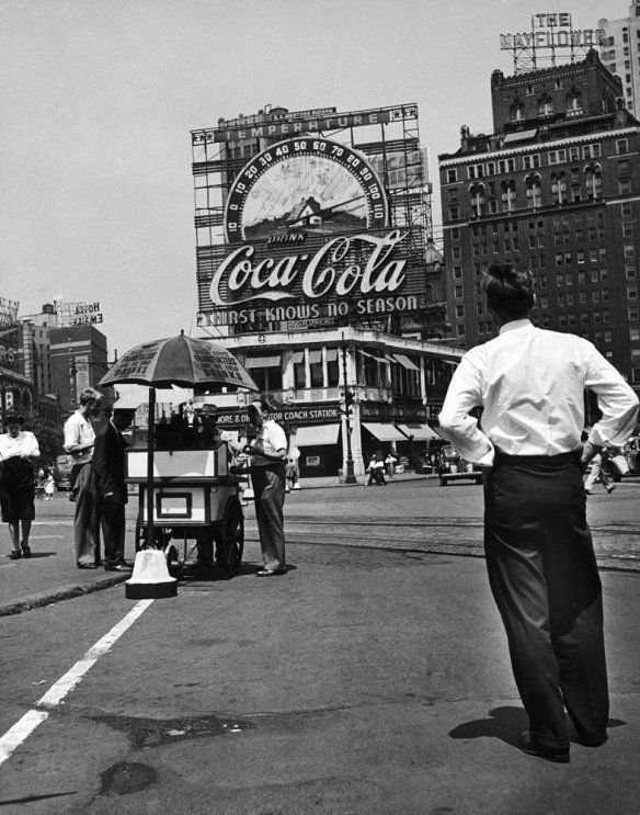 Columbus Circle during a heat wave in August 1944. A large Coca Cola sign and thermometer registers 100 degrees on top of building next to the Mayflower Hotel, New York