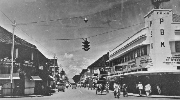 De Groote Postweg gezien in oostelijke richting vanaf het zuidelijk deel van de Pasar Barou straat te Bandoeng (West-Java). Op de achtergrond bomen van het Aloon Aloon (plein). 1920-1939