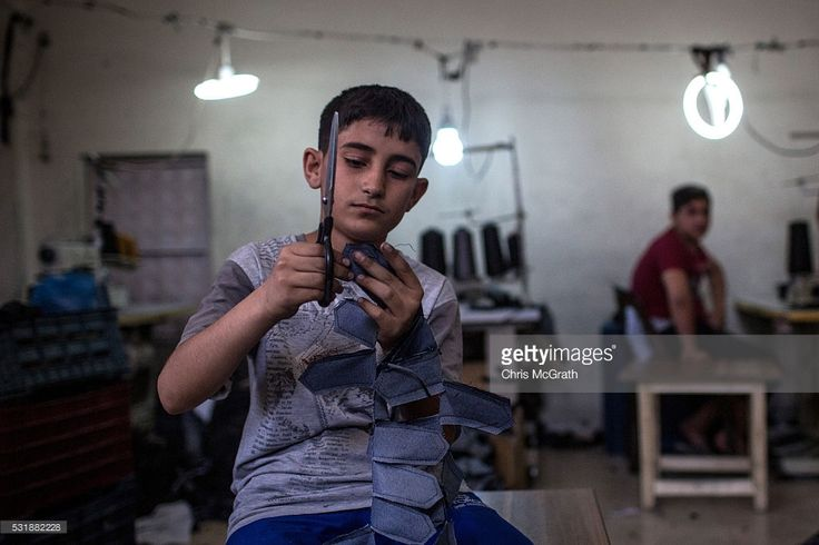 A Syrian refugees child works in a Syrian owned clothing factory on May 17, 2016 in Gaziantep, Turkey. Since fleeing the war and after the new E.U - Turkey deal effectively shutting down routes to Europe for many Syrian refugees, living in Turkey has become their only option, however there is very little stable work and little hope of building a future. Turkey's massive and largely unregulated garment industry is an attractive option for Syrians to work both legally and illegally despite low…