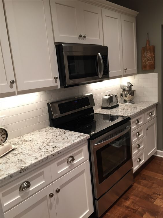 Farmhouse kitchen with shaker style cabinets painted in Sherwin Williams Snowbound. White subway tile backsplash. Sherwin Williams Pavestone on the walls. White Fantasy Granite from Midwest Tile/Marble/Granite in Lincoln, NE: