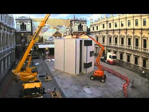 ▶ The multi-storey house Richard Rogers built ... in a day - 'Homeshell' is an innovative, low-cost building built in the courtyard of the Royal Academy in London. It is constructed using Insulshell, a flexible and highly energy efficient building system which could help solve the UK's current housing crisis.  The installation is a three and a half story building delivered as flat-pack panels on a truck and then assembled in just 24 hours on site.