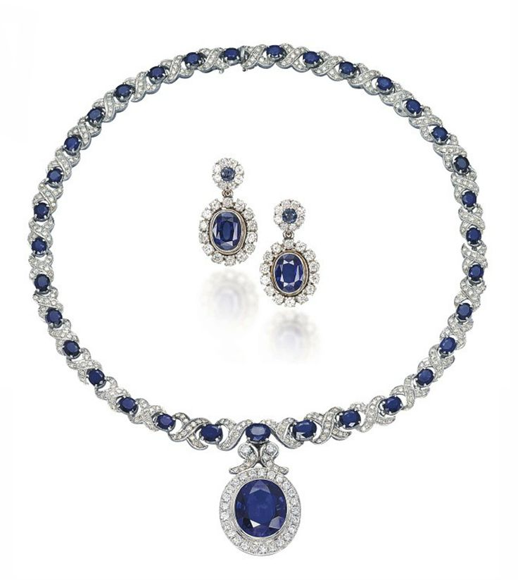 A GROUP OF TREATED SAPPHIRE AND DIAMOND JEWELLERY The necklace designed as a line of graduated oval-shaped sapphires with diamond-set crossover spacers, to the detachable oval-shaped treated sapphire and brilliant-cut diamond pendant of later addition, together with a pair of oval-shaped treated sapphire and brilliant-cut diamond earrings, mounted in gold, necklace 43.0 cm, earrings 3.0 cm