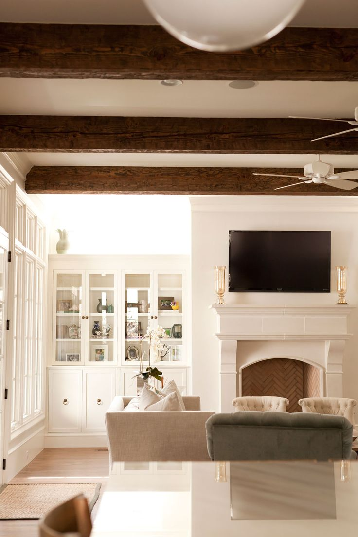 Living room sleek built ins, ceiling beams, cast stone fireplace mantle, cozy elegant rustic