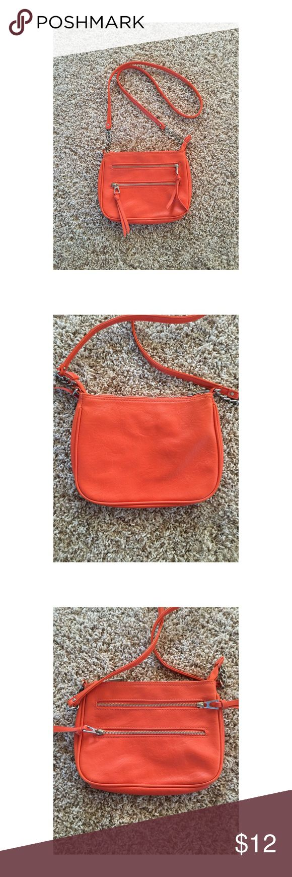orange shoulder bag Silver chain accents and zippers. Three compartments. Two of them are in the outside front and the main third compartment has a small zippered pocket within. Not sure of the brand because it is unlabeled. Excellent condition! Bags