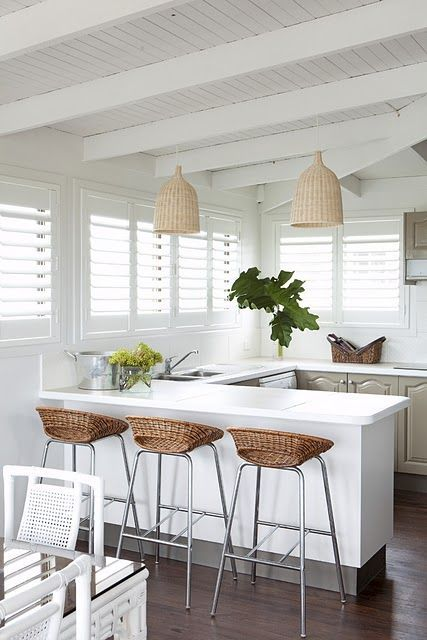 White kitchen, open beams, love the mix of wicker pendants and wicker stools