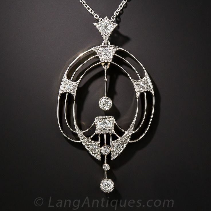 Edwardian Diamond Pendent Necklace. This sensuous and sexy Belle Époque jewel - circa 1910 - artfully incorporates open space, along with platinum (over 18K gold) and diamonds, to achieve a fabulously feminine effect. The central and bottom diamond drops swing freely, from within and below respectively, the curvaceous open pendant. Just shy of 2 inches high by 1 and 1/16 inch wide.