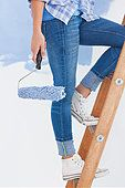 Woman holding paint roller climbing ladder - Stock Photo