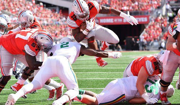 COLUMBUS, OH – SEPTEMBER 12: Ezekiel Elliott #15 of the Ohio State Buckeyes scores on a 1-yard touchdown run past Jerrol Garcia-Williams #2 of the Hawaii ...