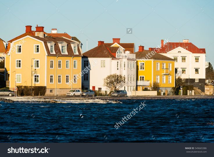 Karlskrona, Sweden - January 5, 2017: Documentary of seaside lifestyle. Lovely seaside homes at Ekholmen, Karlskrona. Cars parked outside on the street and marina visible in the sea.