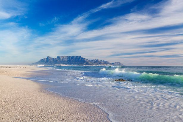 Wave breaking on Melkbosstrand beach with Table Mountain in the background. Western Cape, South Africa