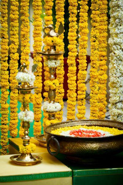 south Indian telegu wedding decor traditional mehendi decor with genda flower strings, brass pots