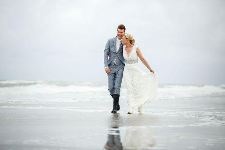 Samen wandelen over het strand met je trouwlaarzen aan.