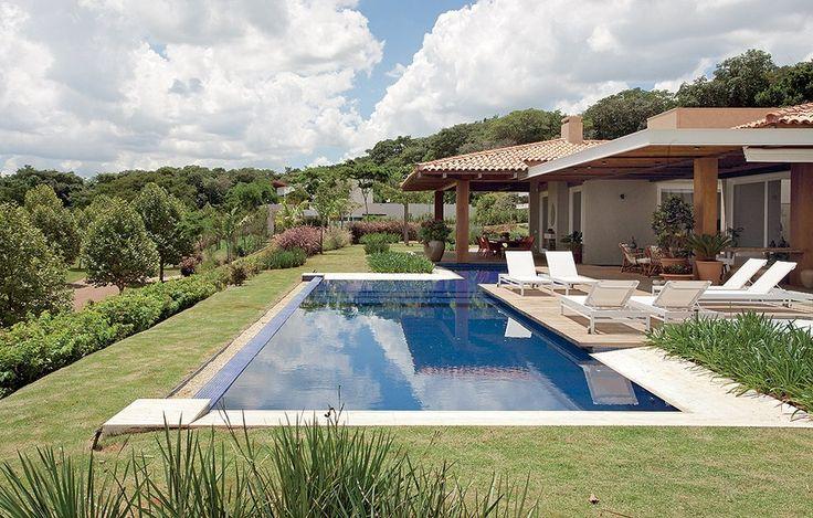 A piscina de pastilhas azuis e borda infinita invade parte da varanda, que dispõe de vista privilegiada. Próximo a sua margem, agapantos, quisquális, hamamélis e moreias preenchem o entorno. Projeto dos paisagistas Sérgio Menon e Caterina Poli