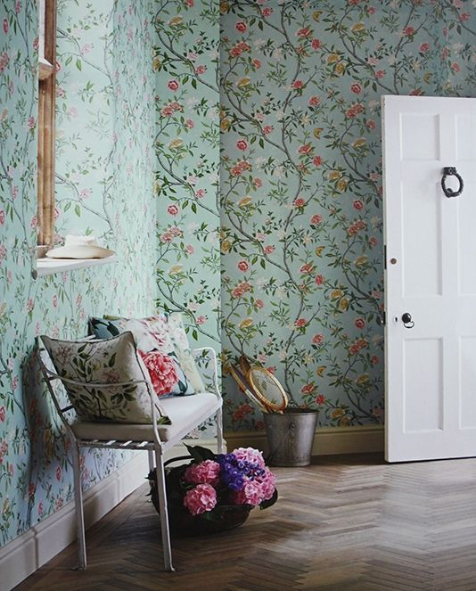 Nostell Priory Wallpaper A floral wallpaper printed with flowing branches with an abundance of flowers and foliage on a blue background.