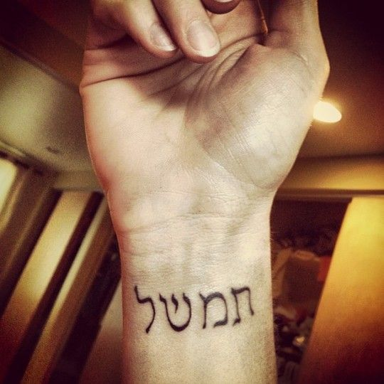 "The tattoo is from John Steinbeck's East of Eden. It means ""timshel"" and it is in Hebrew."