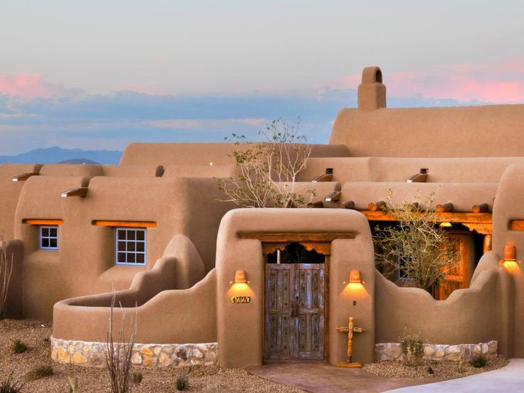 This pueblo revival home designed by Wayne and Kiki Suggs of Classic New Mexico Homes features blue windows to keep the evil spirits out. A traditional rock stem wall borders the adobe courtyard wall, and the room layers are a distinct characteristic of pueblo style, as rooms were added as the family expanded.