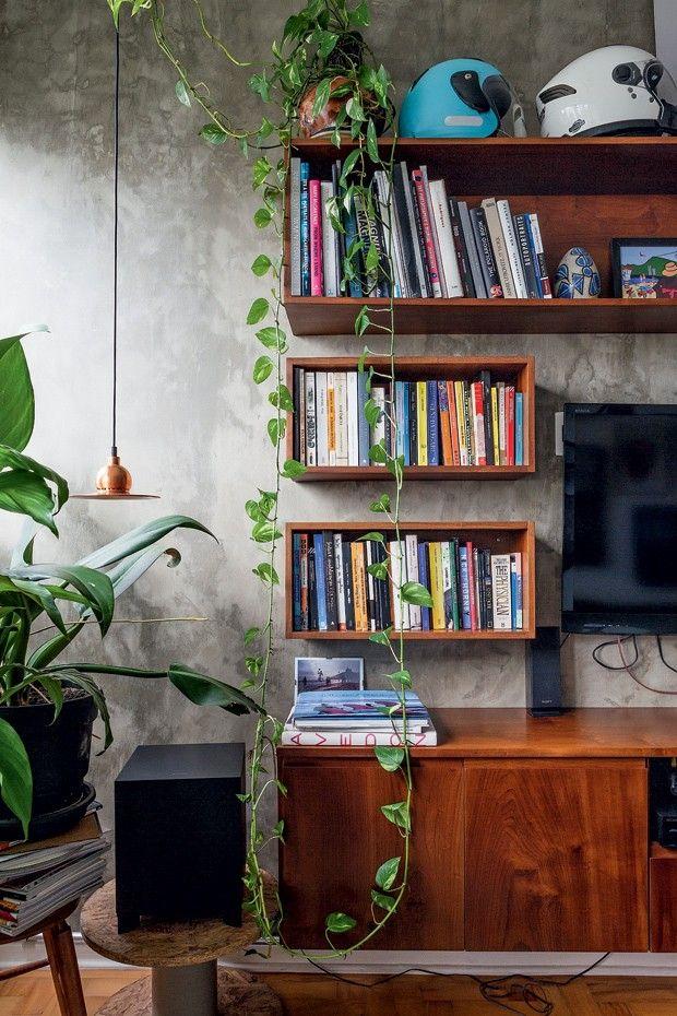 A estante de madeira contrasta com a parede de cimento queimado. Lá é o coração…
