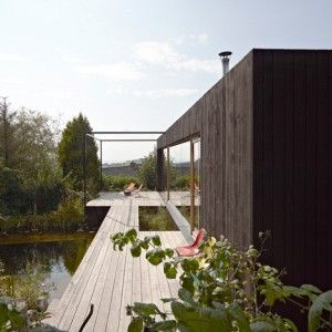 Black house by Hammerschmid Pachl Seebacher  is raised above a bathing lake