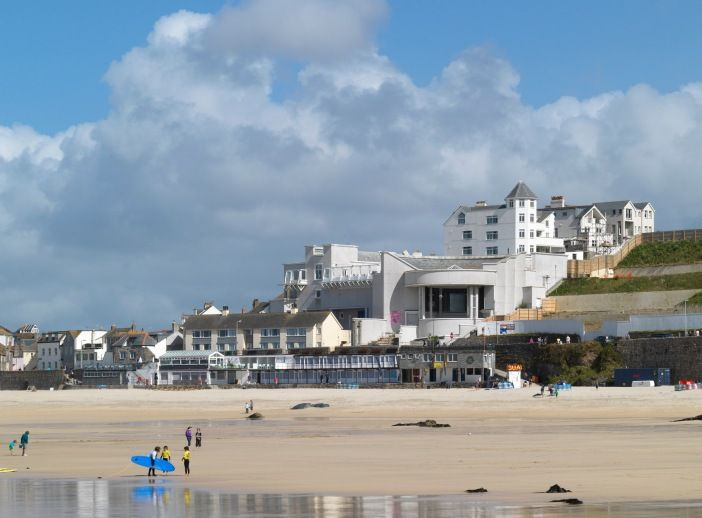 An image showing the beach at St Ives, with Tate St Ives in the background