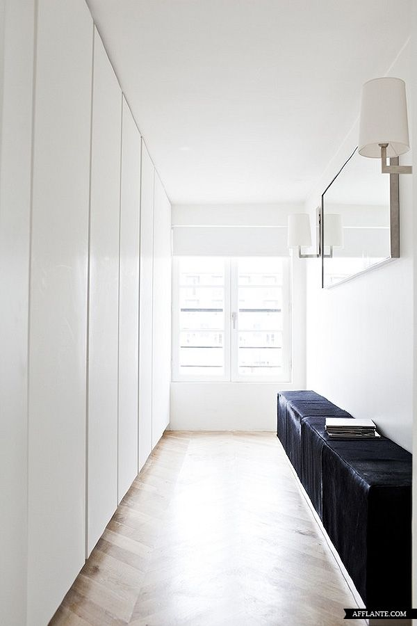 great use of narrow space - wall to wall / floor to ceiling gloss white row of storage