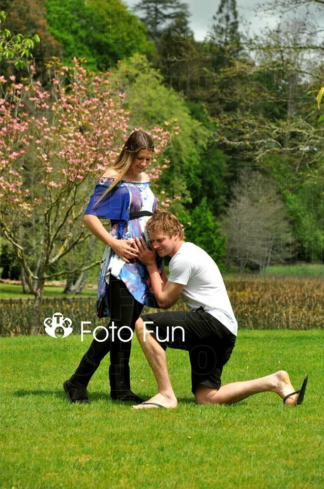 Maternity photos, dad listening to baby in park