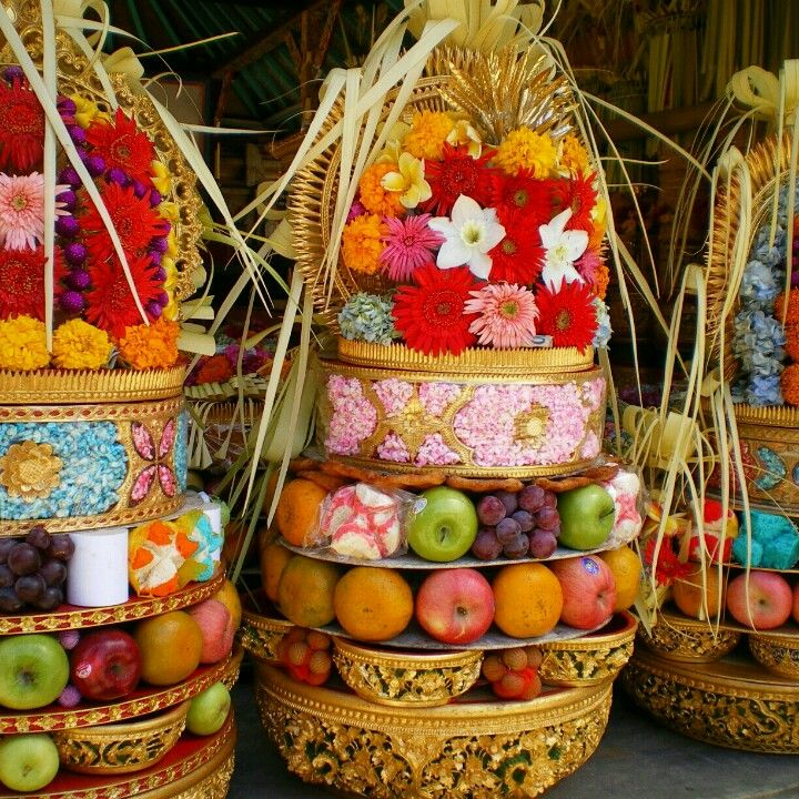 Balinese flower, fruit and cake offerings to the gods are called gebogan. Bamboo skewers pin the fruit etc to a piece of banana tree trunk that runs through the middle of the arrangement.