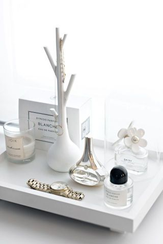 20 minimal and chic ways to elevate your home: Display fragrance bottles and candles on an all-white tray for a pretty way to elevate any tabletop.